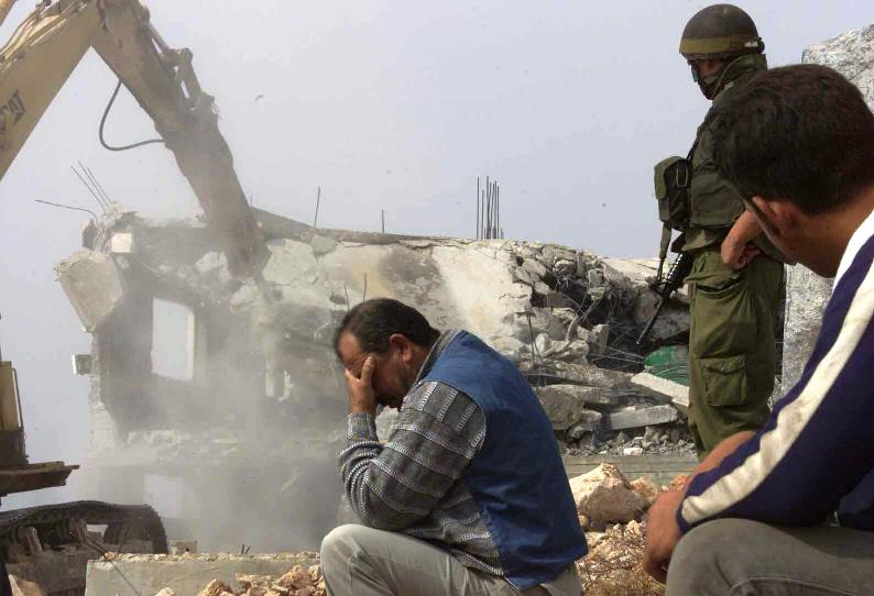 A Palestinian man can't look as his home is demolished by the Israel military.