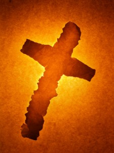 A cross ripped out of a sheet of paper on old paper background. Hot sepia toned.