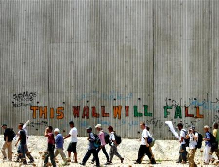 Palestinians and members of the International Solidarity Movement (ISM) walk during a rally along the separation wall in Qalqilya.  Palestinians and members of the International Solidarity Movement (ISM) walk during a rally along the separation wall, part of Israel's controversial security barrier in the West Bank town of Qalqilya August 7, 2004. REUTERS/Mahmoud Shanti